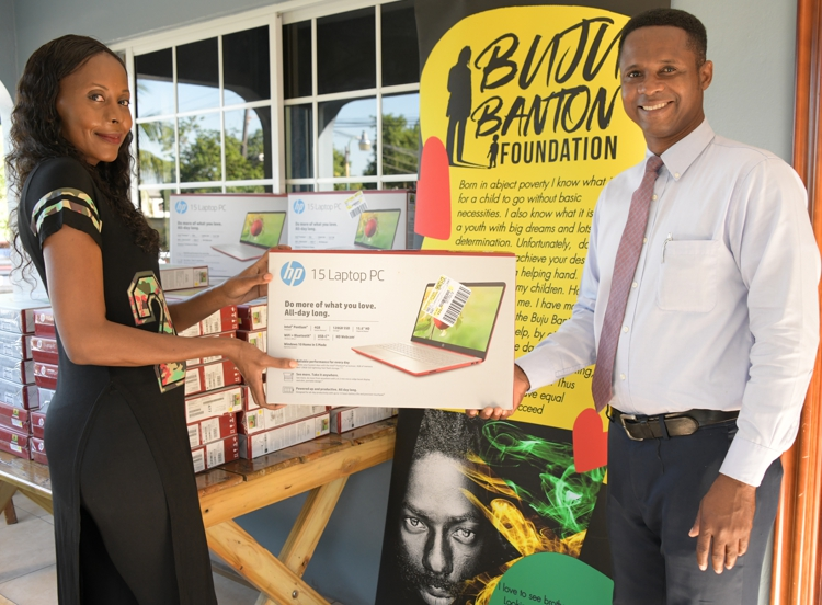 from left- Desmond Whitely, Administrator at Sunbeam Children's Home accepts donation from Rosemary Duncan, Director at Buju Banton Foundation